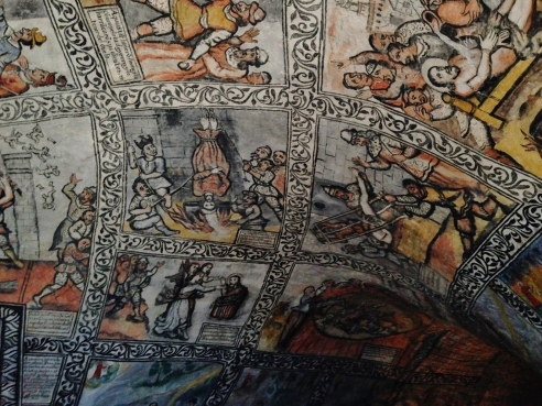 Depictions of Christians being persecuted and saved after praying to God line the walls and cover the ceiling